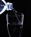 Water. Flows from a bottle in a glass Stock Photos