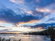 Water abundance at the evening city-pond. During sunset with blue-gold colored landscape Royalty Free Stock Photos
