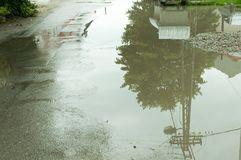 Water accumulate in the puddle on the asphalt road in the hole after heavy rain. Royalty Free Stock Photo