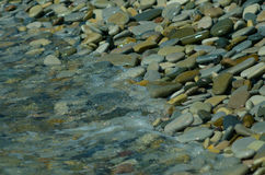 Water accumulates on the pebbly shore. The beach of pebbles. Bac Royalty Free Stock Images