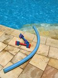 Water aerobics - 4. Two dumbbell weights and one water noodle for water aerobics placed by the poolside stock images