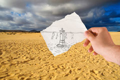 Water for all. Hand holds paper with sketch the fontanelle of water in the middle of the desert Stock Images