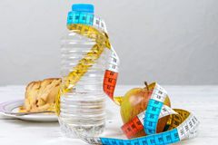 Water and an apple with a measuring tape Stock Photo