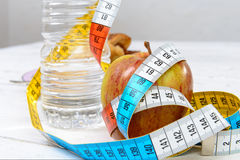 water and an apple with  meter ribbon Stock Images