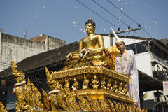 Water around buddha statue. Water flying around a golden Buddha statue during the songkran parade in Chiang Mai, Thailand Stock Photos