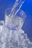 Water att hällas in i ett exponeringsglas Arkivbild