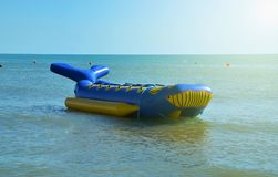 Water attraction `banana` in form of blue smiling inflatable whale. Expects tourists on the Black Sea coast of holidaymakers wishing to ride on calm sea stock photos