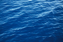 Water Background. Blue water waves under the morning Sun Royalty Free Stock Image