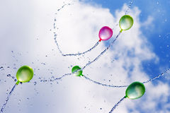 Water Balloons in flight. A group of multi-colored water balloons captured as they fly through the air Royalty Free Stock Photo