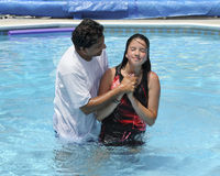 Water Baptism. An Asian Indian pastor baptizing a preteen in a swimming pool