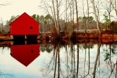 Water barn reflected on lake. Scenic view of red water barn and locks reflected on lake or river in countryside, Virginia, U.S.A Stock Photography
