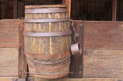 Water barrel on wagon. Wooden water barrel and metal drinking cup on the side of a vintage American chuck wagon royalty free stock images