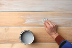 Man hand painting wood surface with blue wood stain. Water based blue wood stain on wood larch board planks royalty free stock images