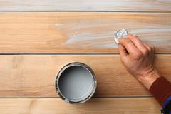 Man hand painting wood surface with blue wood stain. Water based blue wood stain on wood larch board planks stock photo