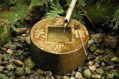 Water basin at Ryoanji. Stone water basin and bamboo pipe at Ryoanji temple, Kyoto, Japan stock images
