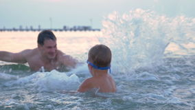 Water battle with dad. Slow motion of a little boy in goggles having sea battle with father. They having fun while splashing water strongly stock video footage
