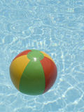 Water beach ball. Red green yellow beach ball floating in a swimming pool Stock Image