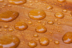 Water beads on treated cedar deck Royalty Free Stock Photos