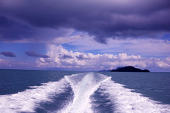 Water behind the speed boat in the ocean with rain clouds sky. Royalty Free Stock Images