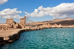 Water of blue lake in mountains near destroyed walls of Zoroastrian fire temple Takht e Soleyman in Iran. Royalty Free Stock Photos