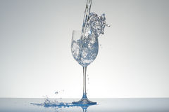Water with blue tint pouring into a wineglass with splashes. Royalty Free Stock Photo