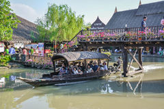 Water boat with tourists floats under the bridge of Thailand cou Royalty Free Stock Photography