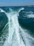 Water boat wake on Michigan lake. Motor boat water wake on Michigan lake, with thin shoreline in background stock photography