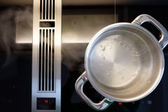 Water boiling in a cooking pot of stainless steel with steam Stock Images
