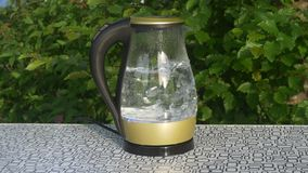 Water is boiling in a glass kettle at camping site stock footage
