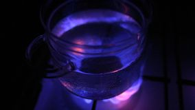 Water boiling in glass pot at gas stove stock video footage