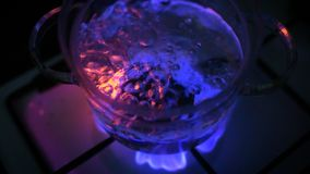 Water boiling in glass pot at gas stove stock video