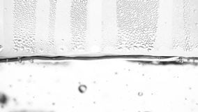 Water boils in kettle. White background. Close up. Slow motion. Bubbles of water from the boil rise. White background. Close up. Slow motion stock footage