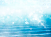 Water, Bokeh, and Flare. Soft focus bokeh light effects over a rippled, blue water background with  lens flare Royalty Free Stock Photos