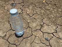 Water bottle on dry and cracked ground Stock Images