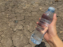 A water bottle on dry and cracked ground Royalty Free Stock Photo