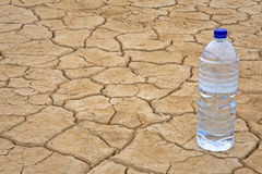Water bottle on dry ground. A water bottle on dry and cracked ground in the desert. Shallow depth of field Royalty Free Stock Images