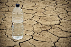 Water bottle on dry ground Royalty Free Stock Photos
