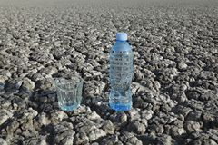 Water in bottle and glass at dry ground. Glass and bottle with clear drinking water at dry cracked land Stock Image
