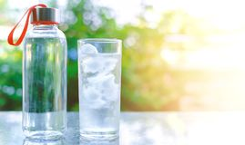 Water bottle and a glass of ice on blurred natural green backgro. Und with copy space and sun light effect for healthy drinking concept Royalty Free Stock Images