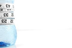 Water bottle healthy diet. Bottle of water with measuring tape on white background. weightloss concept Royalty Free Stock Image