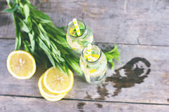 Water bottle with lemon and mint on a wooden table. Royalty Free Stock Image