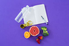 Water bottle, measuring tape, various fruits, vegetable, opened book and pen Royalty Free Stock Photography