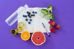 Water bottle, measuring tape, various fruits, vegetable, opened book and pen Stock Photo