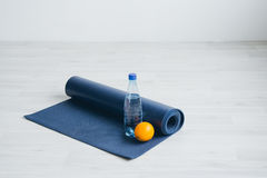 Water bottle, orange, and yoga Mat. Royalty Free Stock Image