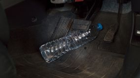 The water bottle rolling hinder car brake ,car safety system on. The feet accident and brake Stock Photos