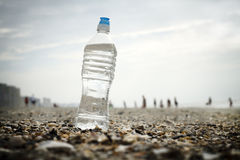 Water Bottle On Shells At The Beach. Low angle view of a single full water bottle sitting prominently among broken shells at the beach on an overcast day. The Stock Photos