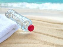 Water bottle and towel on the beach Stock Photo