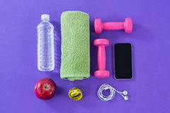 Water bottle, towel, measuring tape, dumbbells, apple, mobile phone and headphones Royalty Free Stock Images