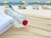Water bottle and towel on the public beach Royalty Free Stock Photography