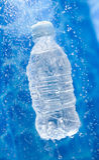 A Water bottle in a water splash. Water bottle dropping ina splash of water drops stock photos